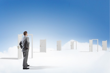 Young businessman choosing one of many opened doors Stock Photo