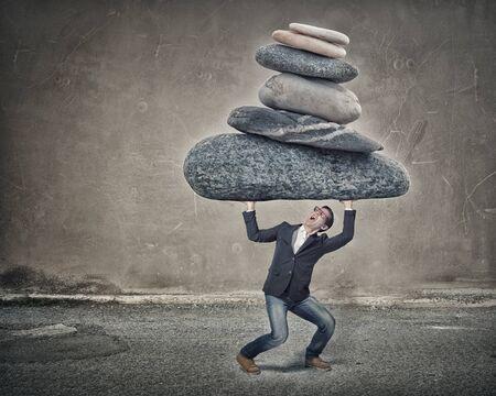 Jonge sterke man met grote stenen boven het hoofd