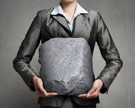 financial burden: Close view of businesswoman holding big heavy stone