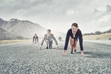 road position: Business people on road in start position ready to run
