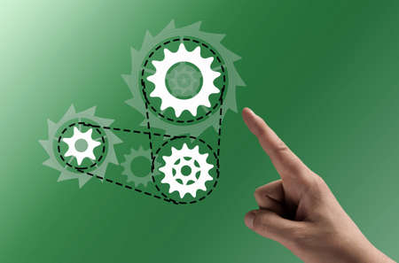 harmonious: Concept of harmonious working mechanism with finger pointing at gears and cogwheels