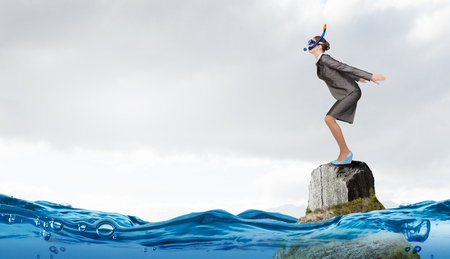 risky job: Young businesswoman in suit and mask ready to jump in water