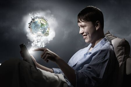 sleeping tablets: Teenager boy in bed using his tablet pc for entertainment. Elements of this image are furnished by NASA Stock Photo