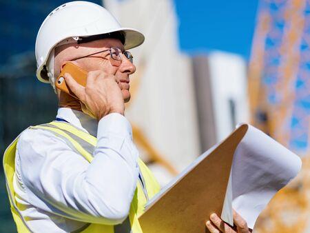 Engineer builder wearing safety vest with notepad at construction site Reklamní fotografie