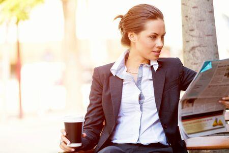 persona leyendo: Retrato de lectura de peri�dicos mujer joven de negocios al aire libre Foto de archivo