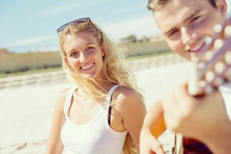 serenade: Happy romantic young couple playing guitar on beach in love Stock Photo