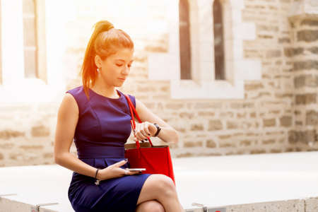hectic: Pretty business woman looking at watch sitting outside