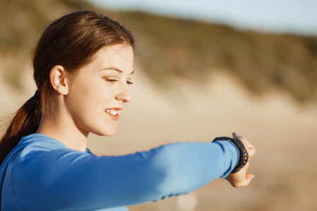 heart rate monitor: Young runner woman with heart rate monitor running on beach