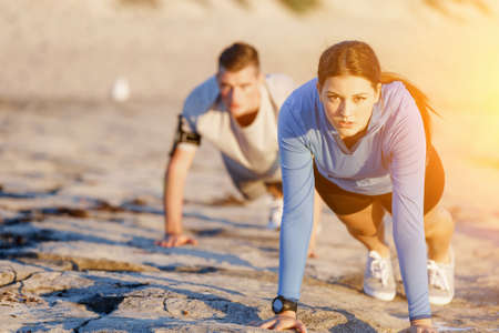 standing up: Young couple of man and woman doing push ups on ocean beach Stock Photo
