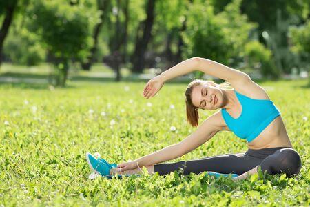 estiramientos: deportivo mujer joven que se extiende en el parque verde de verano