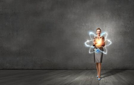 proton: Attractive businesswoman holding glowing atom in hands
