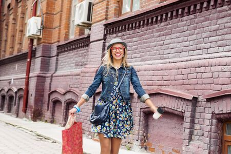 youthfulness: Happy tourist girl with bags and coffee cup walking on city street