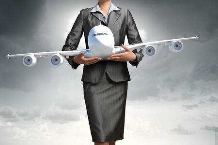 Close up of businesswoman hands holding airplane model
