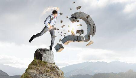 determinism: Emotional businessman destroying with arm stone question mark