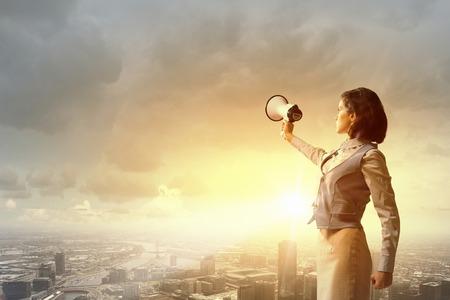 メガホンで何かを宣言するスーツの若い女性実業家 写真素材