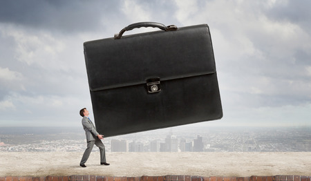 overburdened: Young determined businessman carrying big heavy suitcase Stock Photo