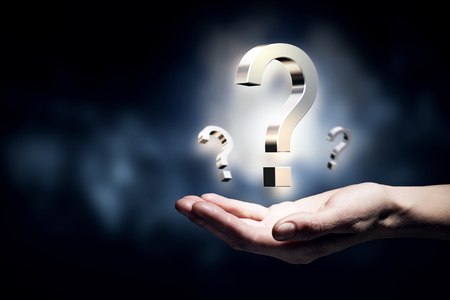 asking question: Hand holding question mark in palms on dark background Stock Photo