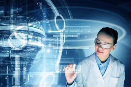 research science: Young woman scientist in glasses touching virtual media screen Stock Photo