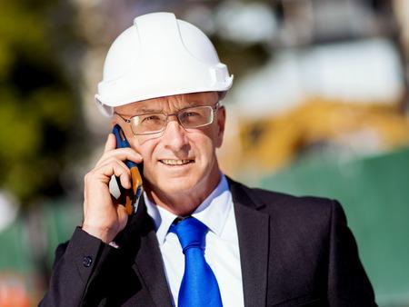 Businesman porter le casque de sécurité avec un téléphone mobile sur le site de construction