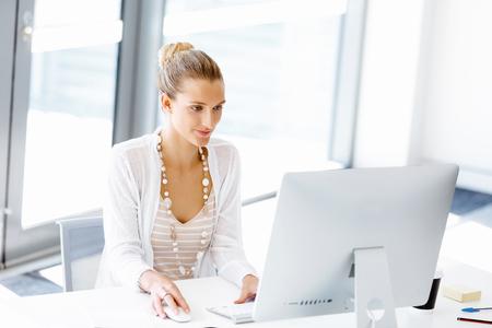 Mulher atraente sentada na mesa no escritório Imagens