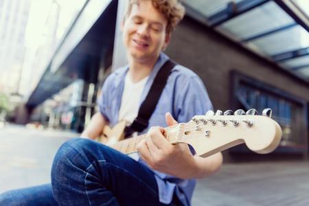musico: Retrato de joven músico con la guitarra en la ciudad