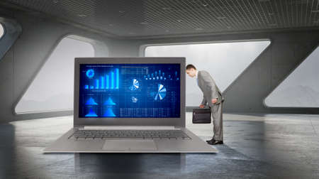 average guy: Young tired businessman and big laptop with infographs on screen