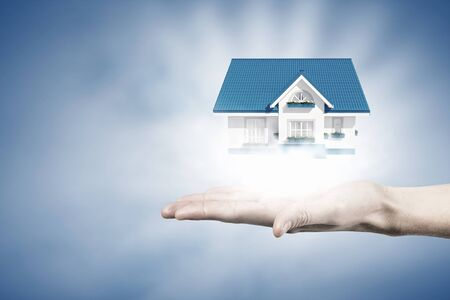 Male hand presenting house model as real estate concept Stock Photo