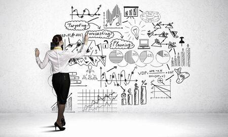 Achter mening van zakenvrouw tekening business plan schetsen op de muur Stockfoto