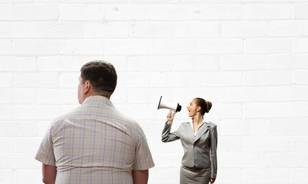 emotionally: Angry woman shouting emotionally in megaphone at man