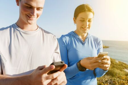 sport wear: Two young people in sport wear with smartphones outdoors