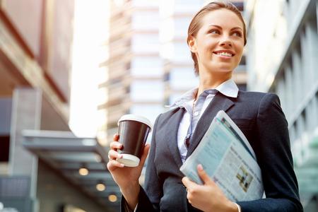 persona de pie: Retrato de mujer de negocios joven que recorre en ciudad