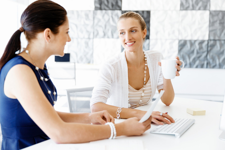 executive women: Two female colleagues working together in office