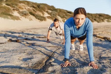 outdoor living: Young couple of man and woman doing push ups on ocean beach Stock Photo