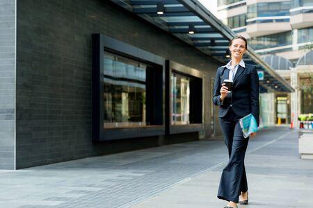 woman walking: Portrait of young business woman walking in city