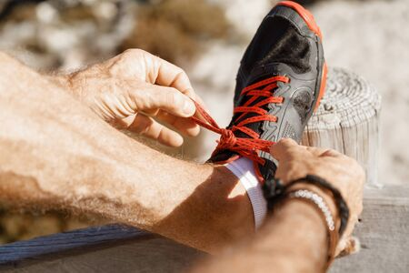 outdoor training: Male runner laces his shoes and prepares to jogging