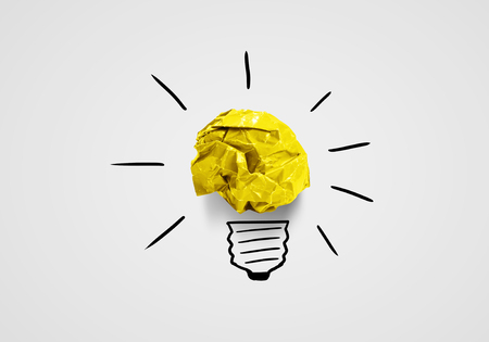 business innovation: Light bulb with crumpled paper balls on white background