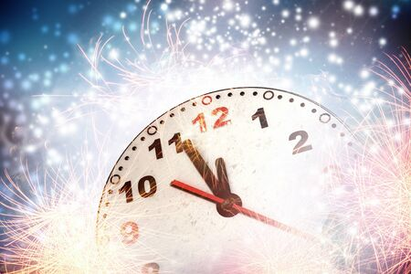12 hour: Clock in bokeh lights showing almost midnight Stock Photo
