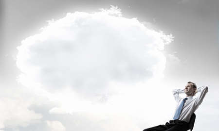 thought cloud: Relaxed businessman with hands behind his head sitting in chair and thought cloud above