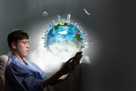 boyhood: Teenager boy in bed using his tablet pc for entertainment. Elements of this image are furnished by NASA Stock Photo