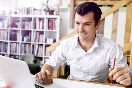 drawing a plan: Male architect with computer studying plans in office Stock Photo