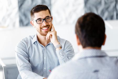 Két jóképű üzletember irodai ül íróasztal, beszéd