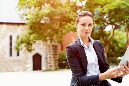 Portrait de femme d'affaires jeune avec ordinateur portable à l'extérieur