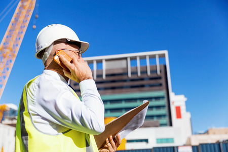 engineering design: Engineer builder wearing safety vest with notepad at construction site Stock Photo