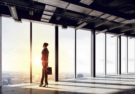 business building: Back view of businesswoman in modern office facing sunrise Stock Photo