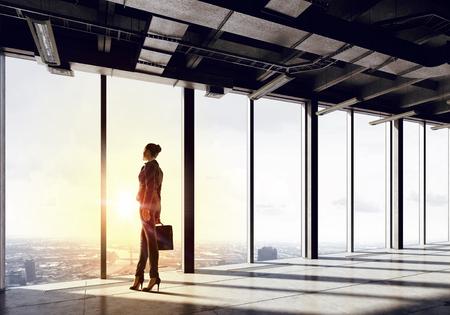 liderazgo empresarial: Vista posterior de la mujer de negocios en la oficina moderna frente a la salida del sol