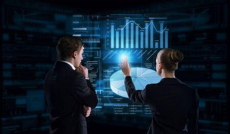 実業家と仮想パネルのインターフェイスの使用のビジネスマンの背面図 写真素材