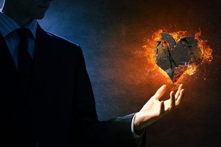 hands fire passion: Stone heart in fire flames in palm on dark background