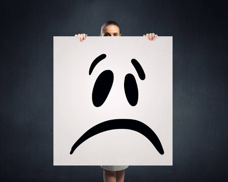 smilie: Young businesswoman showing banner with drawn upset smilie Stock Photo