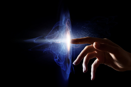 Female finger touching light spot in darkness Stock Photo