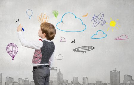 Cute kid boy drawing with marker on wall